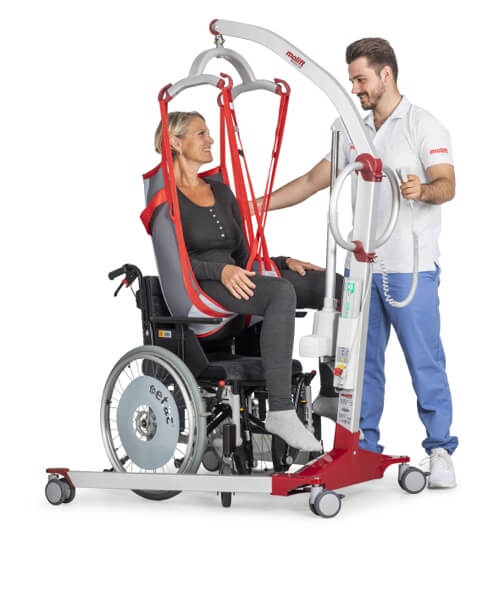 Molift Mover 180 hasta taşıma lifti. tekerlekli sandalye kullanıcısı bir kadını bir hasta bakıcı adam liftle sandalyesinden kaldırmış.